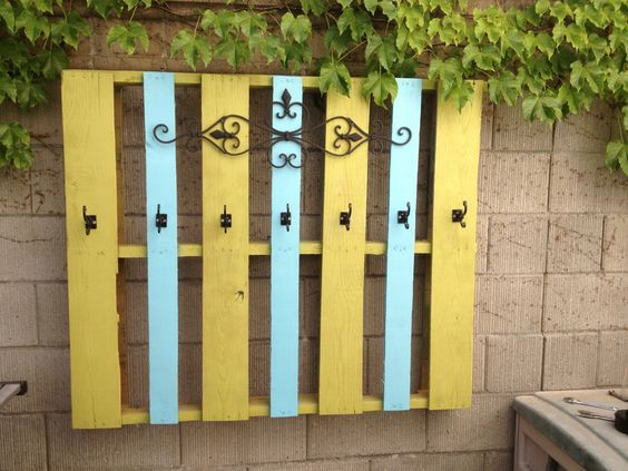 Pallet turned poolside towel holder.  Free pallet, little paint, & Hobby Lobby metal accent and hooks