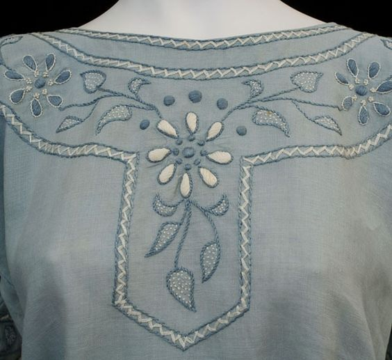 Hand-embroidered linen blouse & skirt, c.1915 $850. Both pieces are hand embroidered with blue and white daisy-style flowers. The highly textured design is a pleasing arrangement of padded satin stitch, French knots, and cross stitch. The blouse and skirt can be worn together as a dress or as separates.