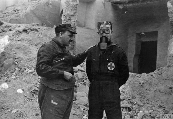Professor J B S Haldane, and his Canadian assistant Hazen Size demonstrate gas masks in front of a ruined house and huge pile of rubble. Hazen Sise is wearing a gas mask as Haldane describes its functions. Possibly Albacete or Madrid.