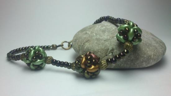Pulsera realizada con bolas superduo en colores metalizados y montada sobre cadena de rocallas y cuentas metálicas color bronce.