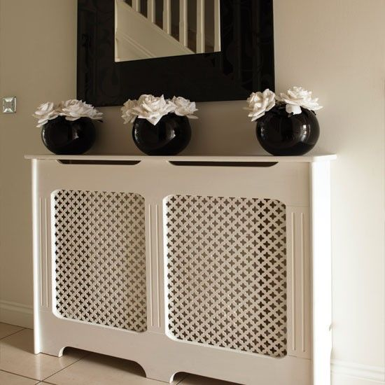 Smart vases, a statement mirror and a painted radiator cover make this hallway more than a walk-through space.