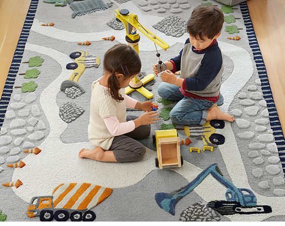 Construction trucks move gravel and orange cones mark the path on this imaginative rug, perfect for a playroom.