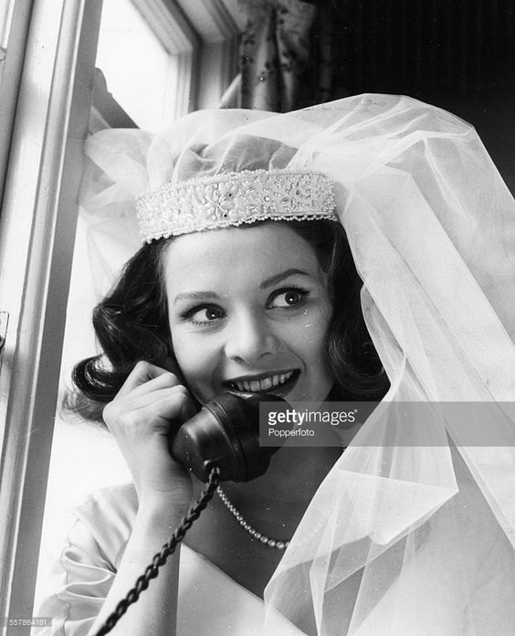 0 British actress Judy Huxtable on the phone, wearing a wedding dress