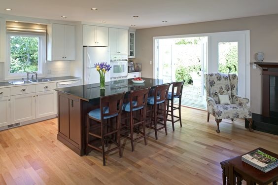 Remodeled kitchen with light, hardwood floors, white appliances and cabinets in back, a double oven and a large, dark kitchen island to offset the brighter colors. Click on the image to see all the benefits of kitchen remodels. #smallkitchen #kitchenisland
