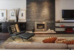 Modern Living Room with Built-in bookshelf, Eldorado Stone LedgeCut33, metal fireplace, Pavilion Leather Chair and Ottoman