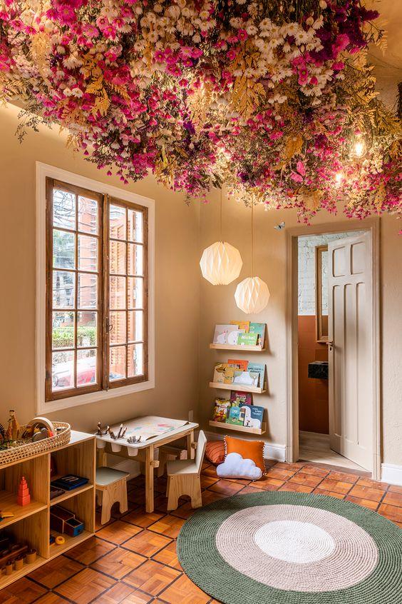 Espaço Montessori, de Silvana Martino (Bá Cla Arquitetura Infantil) + Muskinha + Mini Moo. O quarto montessoriano tem tapete redondo, móveis baixos para que as crianças tenham autonomia, marcenaria para aquecer o ambiente. No teto, as flores ficam expostas em arranjos ousados.