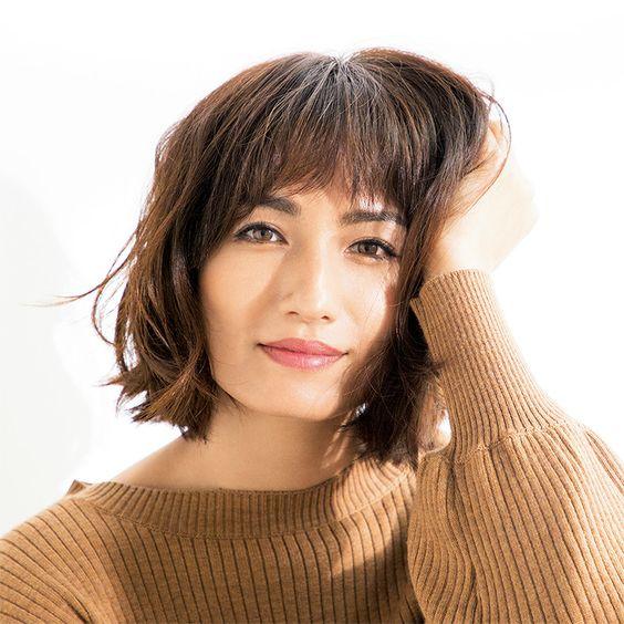茶色いニットを着て微笑んでいる佐田真由美の画像