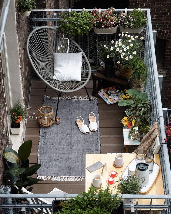 On aménage son balcon avec un fauteuil et des plantes pour un endroit cosy.: