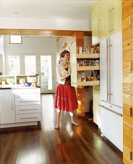 Eine moderne, offene Küche mit Hochschränken und Apothekerschrank ...