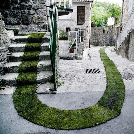"""Dans le village de Jaujac en Ardèche, la plasticienne marseillaise Gaëlle Villedary a réalisé """"Tapis Rouge"""", une installation éphémère réalisée à partir de 168 rouleaux de pelouse. Un ruban de gazon de plus de 400 mètres traverse ainsi le vill..."""