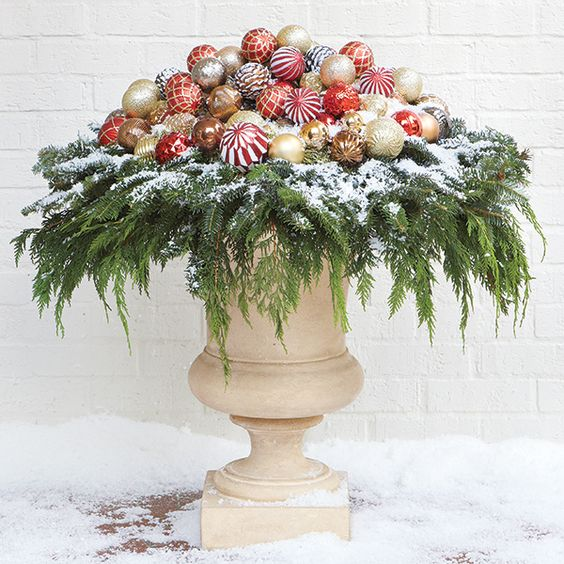 urn-style containers covered with leaves and Christmas balls #christmas  #containers #planters #gardenplanters #christmasBall