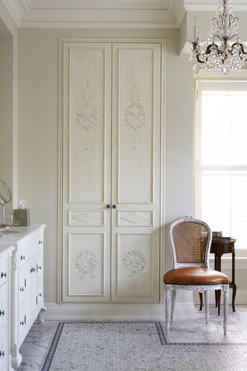 French inspired bathroom features recessed linen cabinet with painted doors situated next to white footed French vanity topped with white marble atop white marble tiled floor adorned with marble herringbone inset tiles with gray marble border.