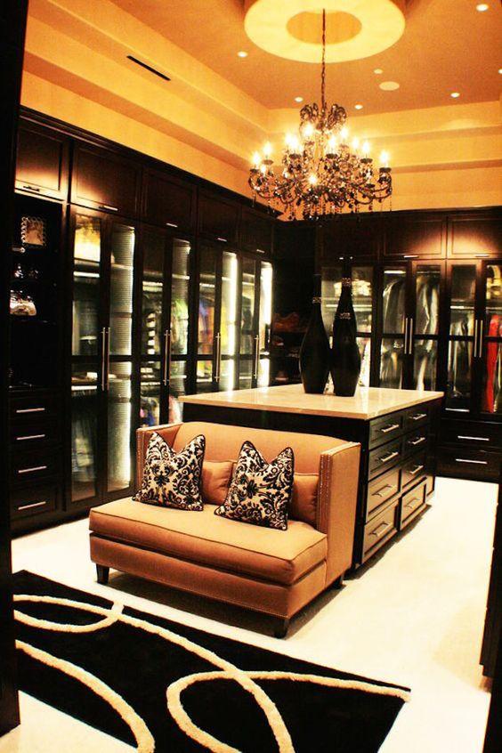 Glamorous walk-in closet with glass closet doors with dark wood, sofa and island table #glass #cabinets #closet #storage #organization #allenrothCloset #allenAndRothCloset #closetShelves