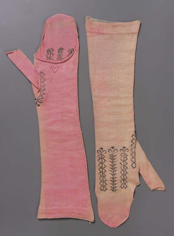 Pair of mitts, probably France, late 18th century. Salmon pink silk knit with metal thread embroidery.