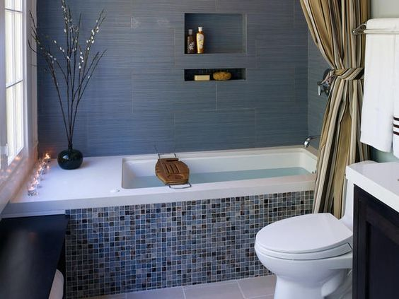 Eco-friendly materials were used throughout to create this Zen spa retreat. A recycled glass mosaic tub face has accents of brown to complement the dark wood vanity in the bathroom. A floor-to-ceiling shower curtain allows a small space to appear much larger.