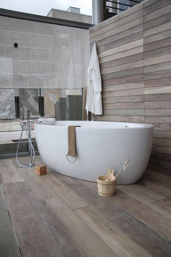 une baignoire ilot, en acrylique, posée sur un carrelage imitation parquet, une imitation parfaite,d'un bois de récupération noueud a souhait. Le décor assorti chalet, vous permet de donner un effe [...]