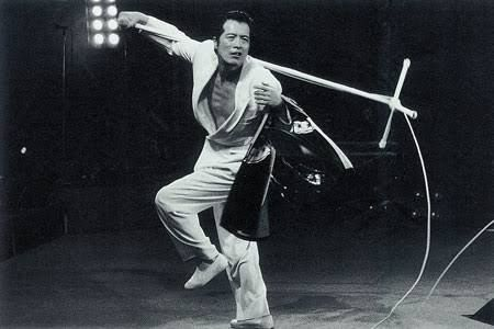 白いジャケットを着てスタンドマイクを担いでいる矢沢永吉の画像