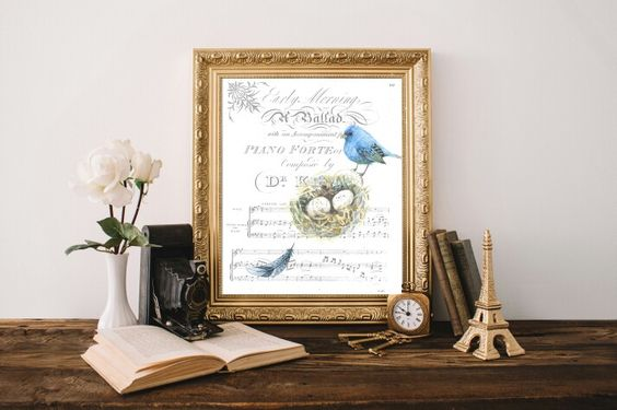 Watercolor songbird, nest, and feather on vintage sheet music. Visit penpaperandpetalsstudio.com