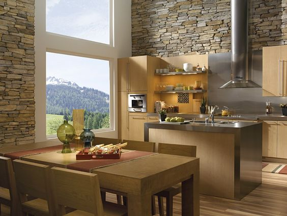 Contemporary kitchen with stainless steel appliances and stone walls, floor to ceiling windows