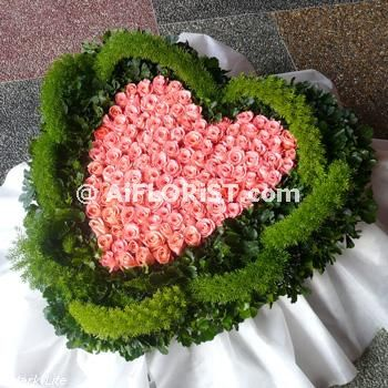 Deluxe heart shape funeral flower arrangement of Imported Roses approx. 99 stalks of Pink Roses surrounded by some Tea Leaf. Kindly specifly preferred colour if not as shown.