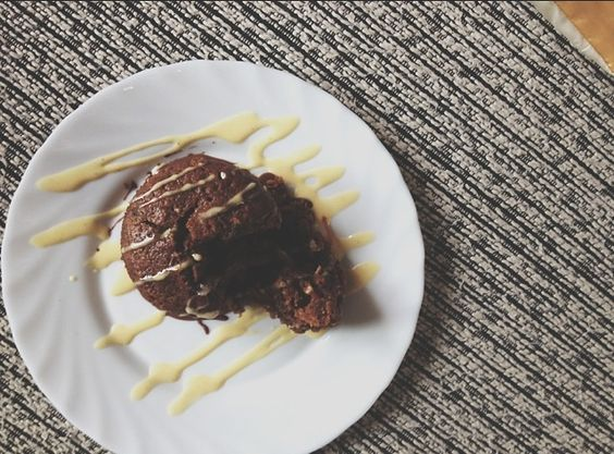 homemade carrot cake topped with chocolate and vanilla sauce