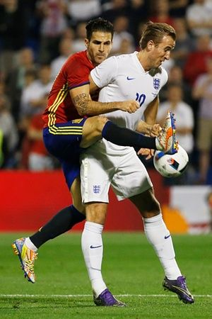Harry Kane shields the ball from Cesc Fábregas.
