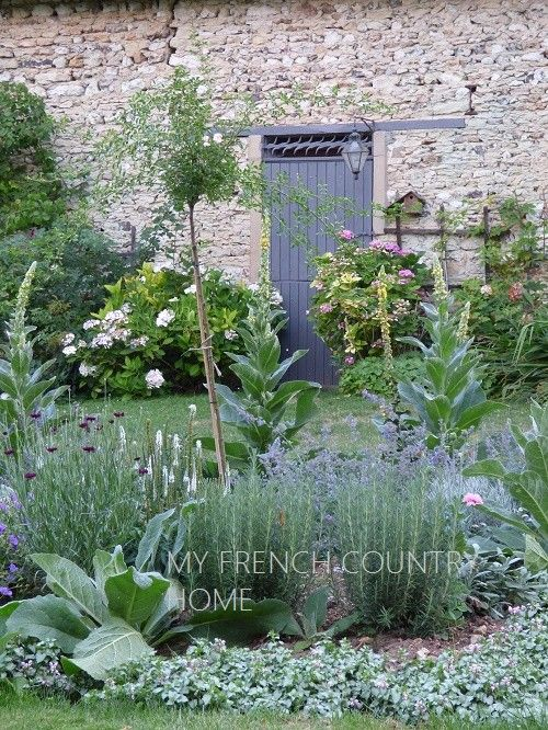 french country flower beds in front of stone barn