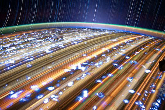 these photos offer us a glimpse of Earth from the International Space Station. As the ISS circles Earth at roughly 17,000 miles per hour, Flight Engineer Don Pettit takes 30-second exposures with a stock digital camera, then stacks those exposures into single frames that capture 10-15 minutes on the ISS. The rotation is fast enough for long exposures to blur the earth into gilded landing strip beneath a steady rain of stars