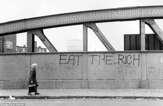 A woman walks past this slogan on a bridge - where there is also support for London football club Queens Park Rangers.