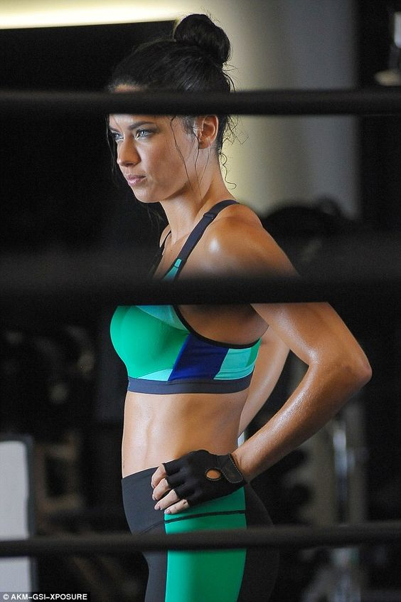 Amazing tone: The bronzed stunner was working it hard during the photo session while displaying her physique in a green and black sports bra and leggings