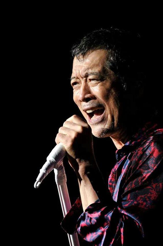 赤と黒のシャツを着て歌っている矢沢永吉の画像