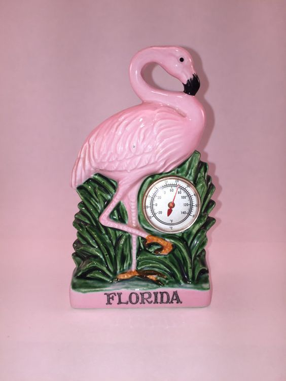 This is a wonderful souvenir of someones past trip to Florida. A bright pink Flamingo posed on one leg in tall grass. He stands just about 6