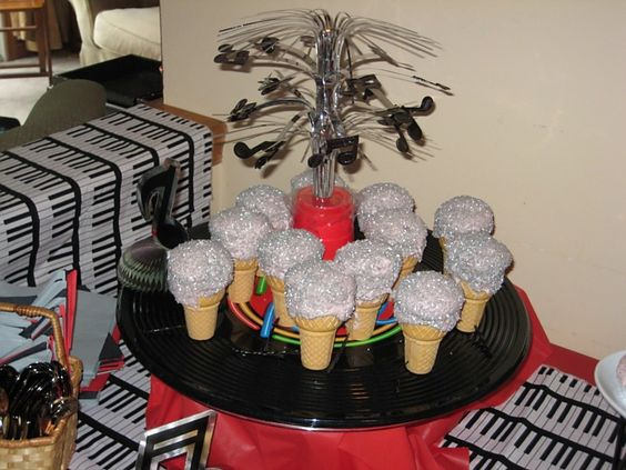 I made Microphones by baking cupcakes in ice cream cones. I covered the white frosting with silver sugar that gave it a look of the top of the microphone. I also put a small hole at the bottom of the cones and added a piece of black shoe string licorice to simulate the cord coming from the microphone.