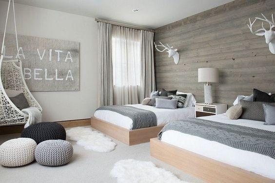 chambre scandinave grise avec fauteuil gamac, trophées déco et poufs