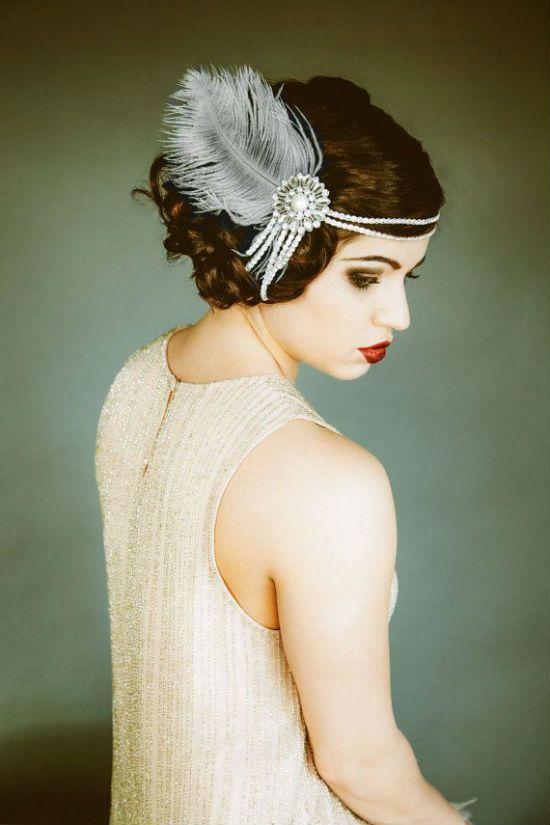 Les cheveux bouclés sont attachés en chignon très fluide : une mèche revient sur le front. La chevelure est agrémentée d'un head band majestueux constitué de deux rangs de perles blanches, d'un grand bijou composé de ces mêmes perles en forme de rosace et de rubans, et enfin d'une gigantesque plume blanche. Avec un tel accessoire, vous ne passerez pas inaperçue ! Pour compléter ce look « Gatsby le Magnifique », rien de tel qu'un maquillage prononcé et une robe droite écru à strass comme ici.