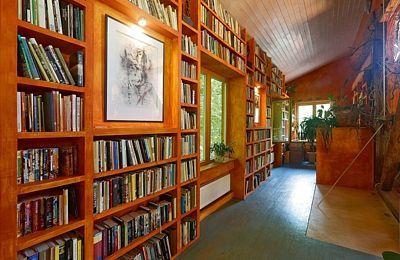 Stěnu chodbičky nad posezením zabírá rozsáhlá knihovna.