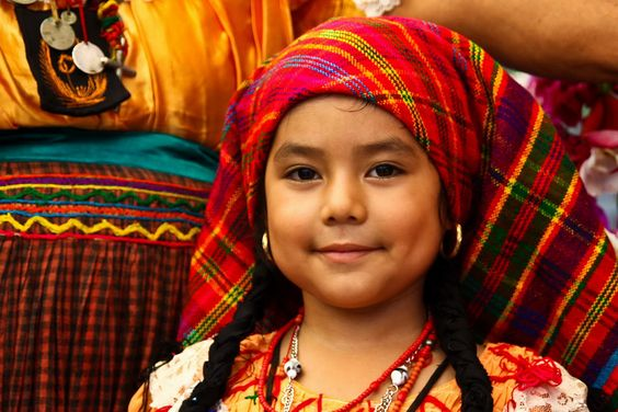 A young Pipil girl dressed in traditional regalia during the Flower and Fronds Fair, a religious celebration of devotion towards the Virgin Mary.