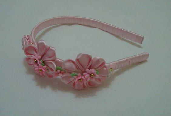 Tiara revestida em fita cetim rosa, com flores em fita cetim, rosinhas de biscuis e lacinhos. R$ 10,00