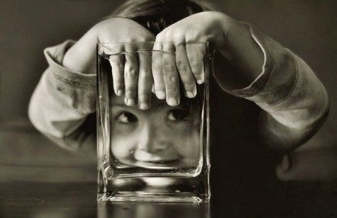 Young boy playing with glass vase transparency