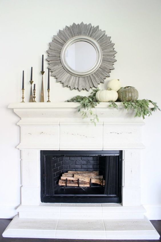 Fall mantel ideas for a minimal look using candles, pumpkins, and a mirror