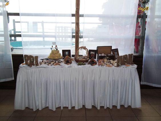 Mesa do bolo, bem-casados e lembranças dos padrinhos decorada com cesta, letras forradas de estopa, baú, búzios e porta-retratos