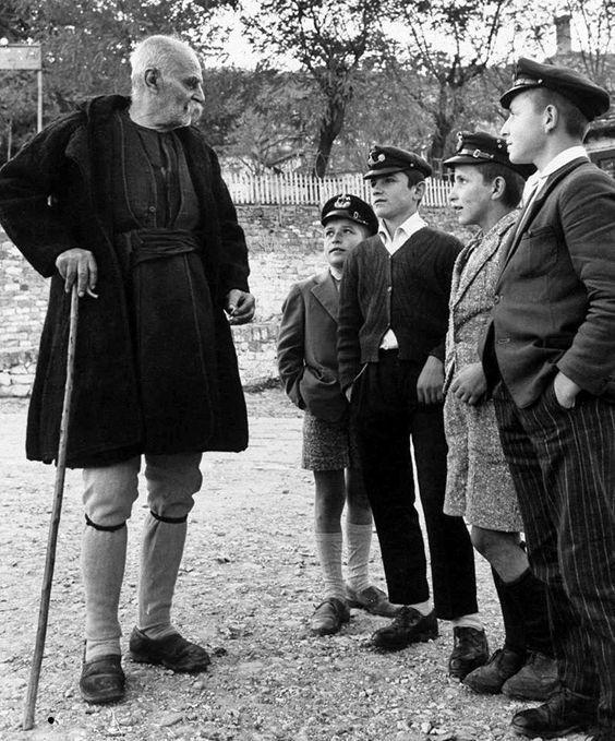 Γέροντας σε συζήτηση με νεαρούς. Νοέμβριος 1959 - James Burke, Μέτσοβο, Τρίκαλα, Θεσσαλία