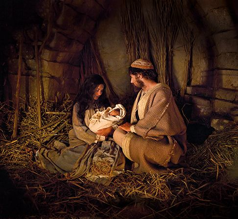 Joseph and Mary hold the baby Jesus on the night of His birth.: