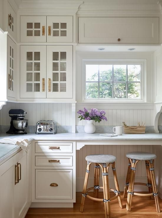 Under A White Shaker Overhead Cabinet A Window Is Flanked By Glass Front Cabinets Donning Antique Bras Glass Front Cabinets Bistro Stools French Bistro Stools