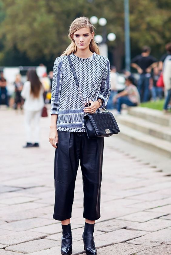 Leather culottes and printed top accessorized with a crossbody bag and leather boots.