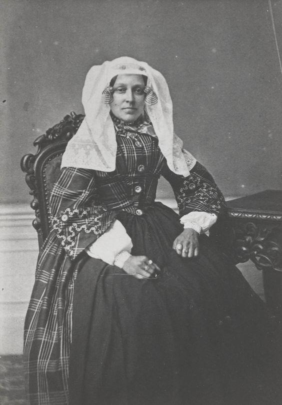 Vrouw in streekdracht uit Oud- Beijerland. Ze draagt de 'lange muts', met daaronder een oorijzer met wijde gouden krullen aan de uiteinden. Naast de krullen is een paar mutsenspelden in de muts gestoken. Ook bovenin de muts is een paar spelden gestoken. Ze draagt een geruite japon, met losse ondermouwen en een schort. ca 1865 #HoekseWaard #ZuidHolland