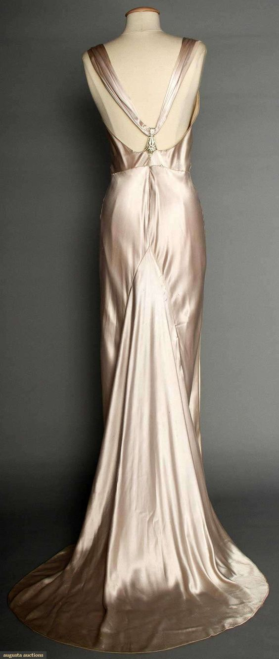 "SILVER SATIN EVENING GOWN, 1930s Pale lavender/silver silk charmeuse, bias-cut, sleeveless, cowl neckline, open back, jeweled Deco elements on shoulder straps & at CB, floating trained back panel, labeled ""NRA Code, Made Under Dress Code Authority PHB038577"""