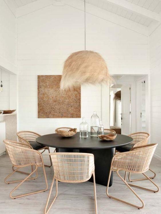 Scandinavian dining table with natural materials like feathers. Runt matbord i naturmaterial. Fjäderlampa och rottingstolar.