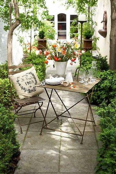 Sur la terrasse d'une maison de ville, les deux longueurs sont aménagés avec des arbustes et deux jarres anciennes dans le fond pour faire le plein de verdure.