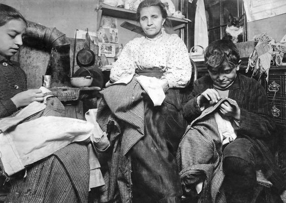 Vintage Photos: Lewis Hine - Tenement Workers High up on the top floor of a rickety tenement, this mother and her two children were living in a tiny one room, and were finishing garments, New York, 1912